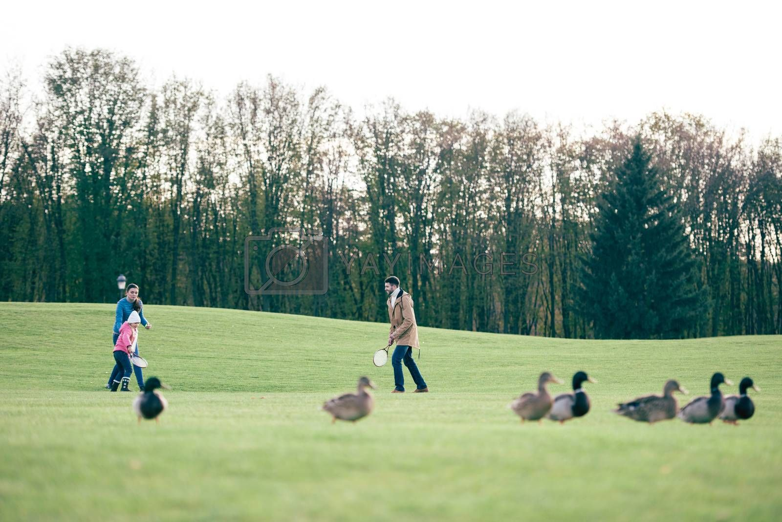 Happy family playing badminton on green lawn at sunny autumn day