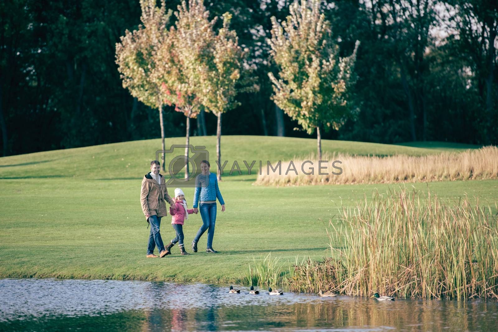 Happy family walking near lake by LightFieldStudios