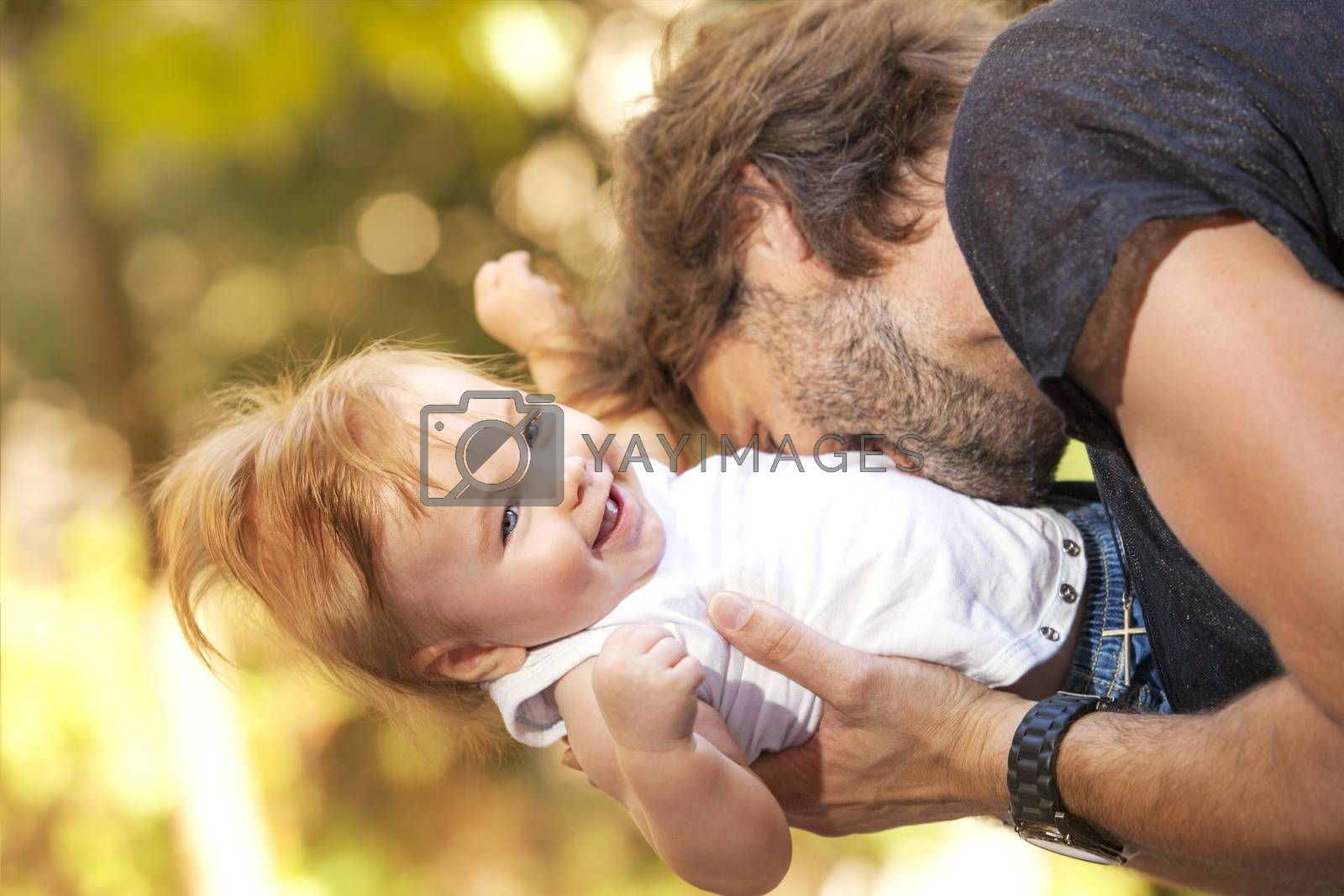 A cute little baby is laughing while his father is biting him playfully outdoors.