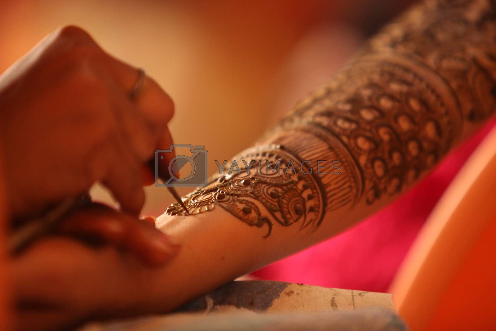 An artist making a beautiful henna or mehendi design on the hand of an Indian wife.
