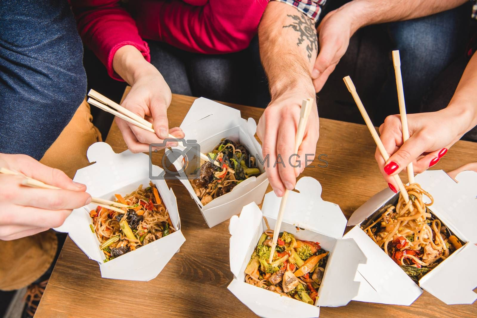 Partial view of people eating noodles with chopsticks