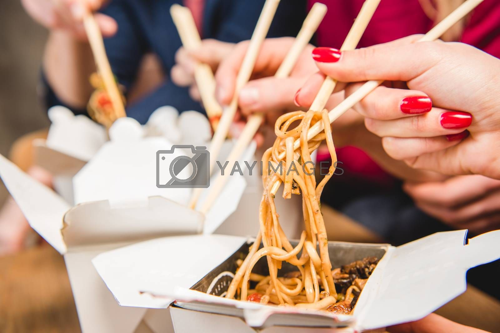 Close-up view of people eating noodles with chopsticks