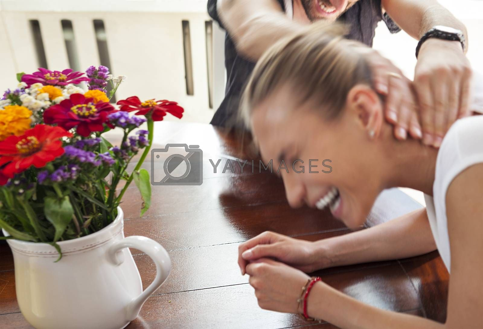 Motion blurred figures of playful young couple indoors. The man is squeezing the woman s neck. Female is laughing.