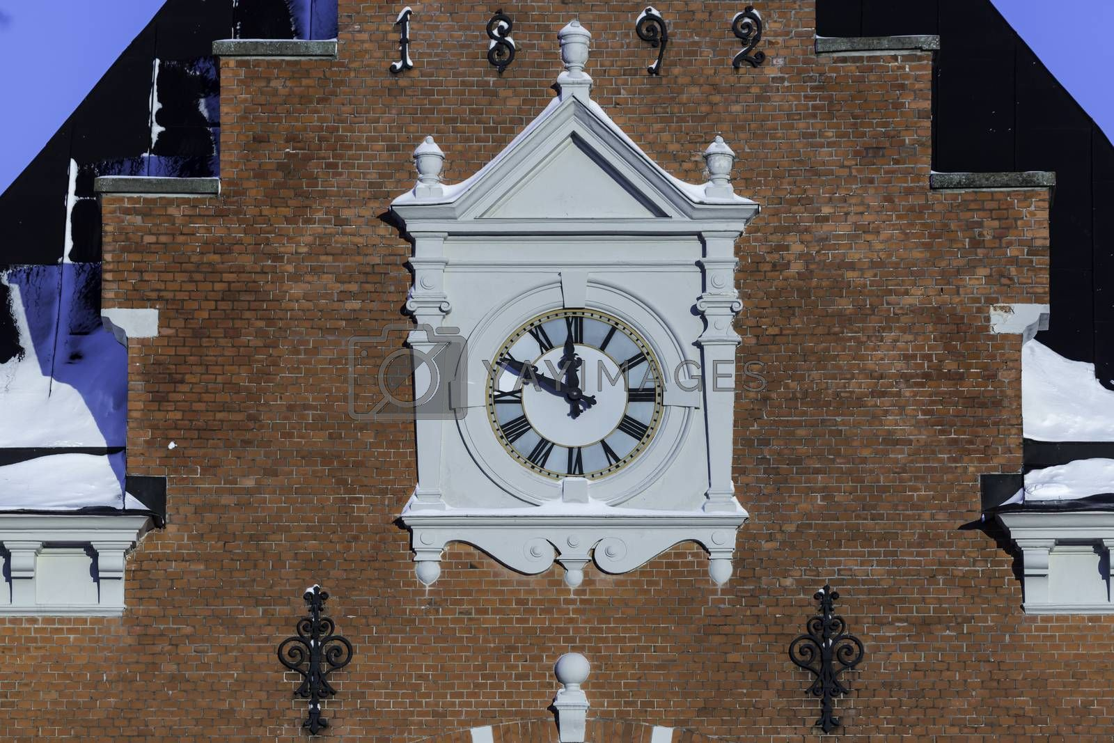 The Clock on the Umea, Sweden Town House close up with snow.