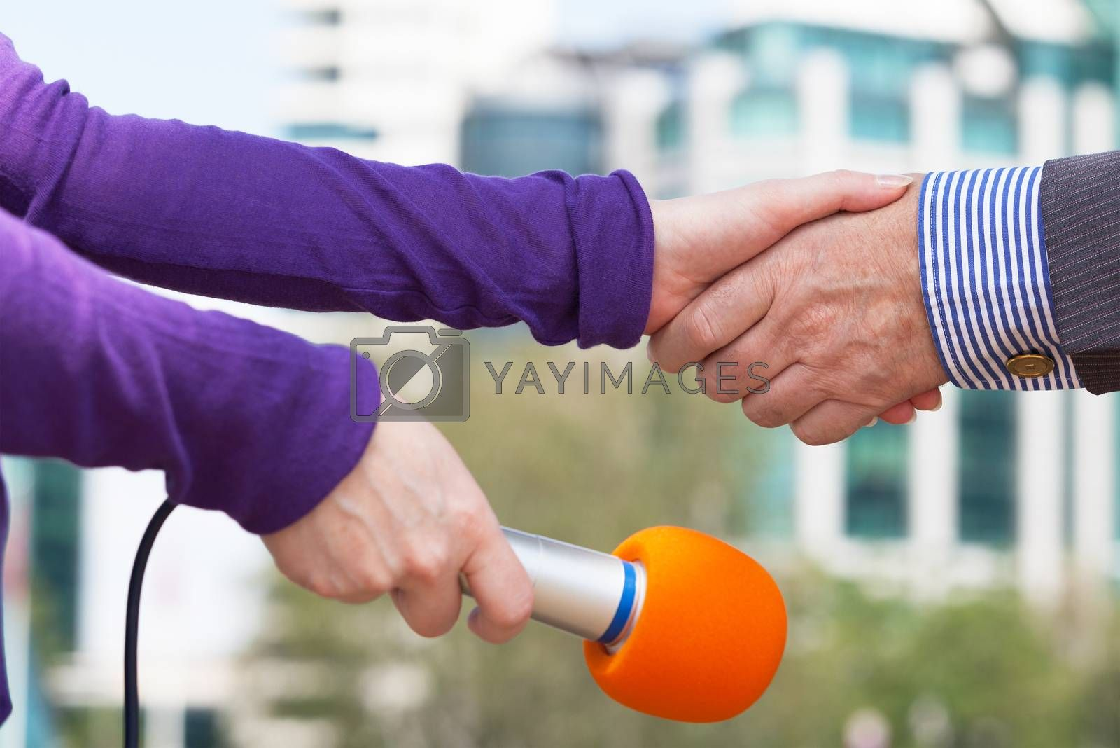 Businessperson and a female journalist shaking hands before media interview