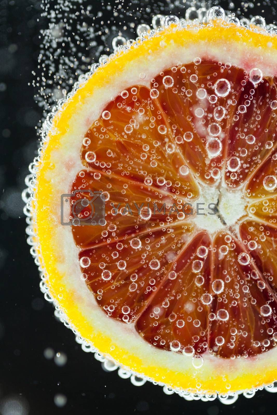 Close-up of blood orange slice diving into carbonated water with bubbles on black background. Refresher drink concept