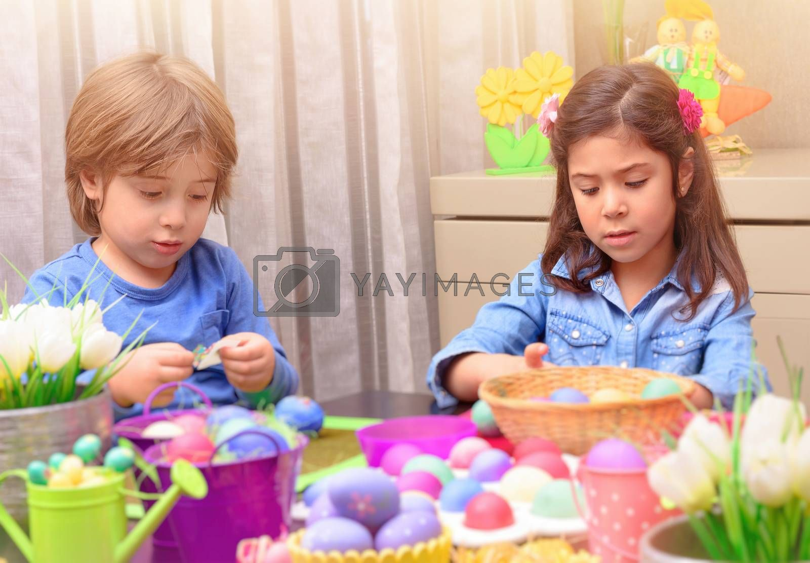 Portrait of little brother and sister painting traditional Easter eggs in different colors at home, with pleasure preparing to religious spring holiday