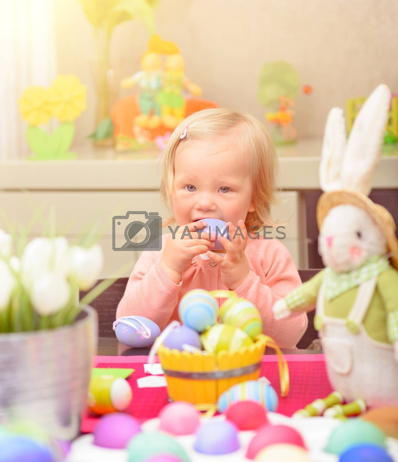Adorable playful little girl coloring eggs for spring religious holiday, sitting near bunny toy, celebrating Easter at home