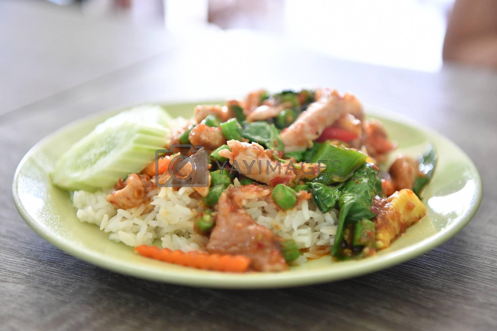 Stir fried pork and curry paste on rice, Thai food.
