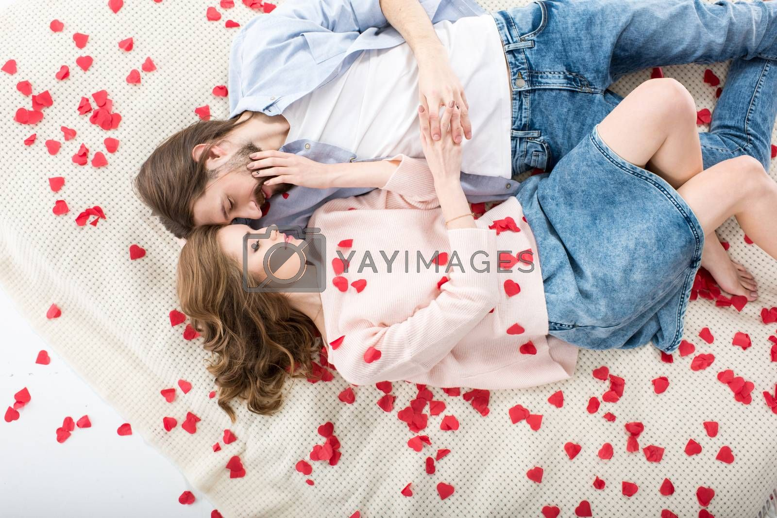 Beautiful couple in love lying and touching each other on red paper hearts