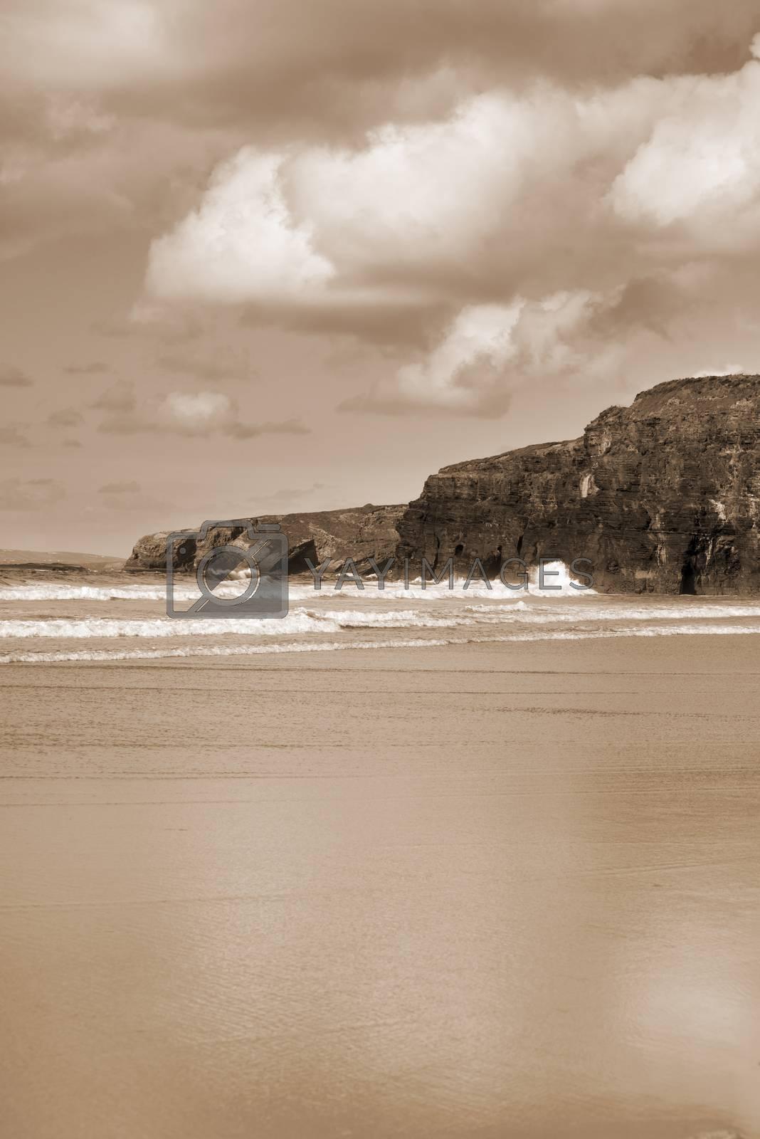 beautiful soft waves break on the beach cliffs at ballybunion