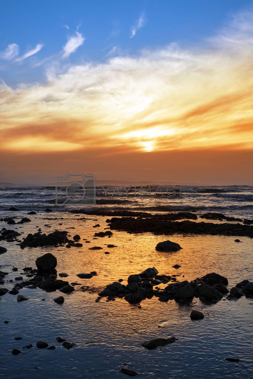 reflections at rocky beach near ballybunion on the wild atlantic way ireland with a beautiful yellow sunset