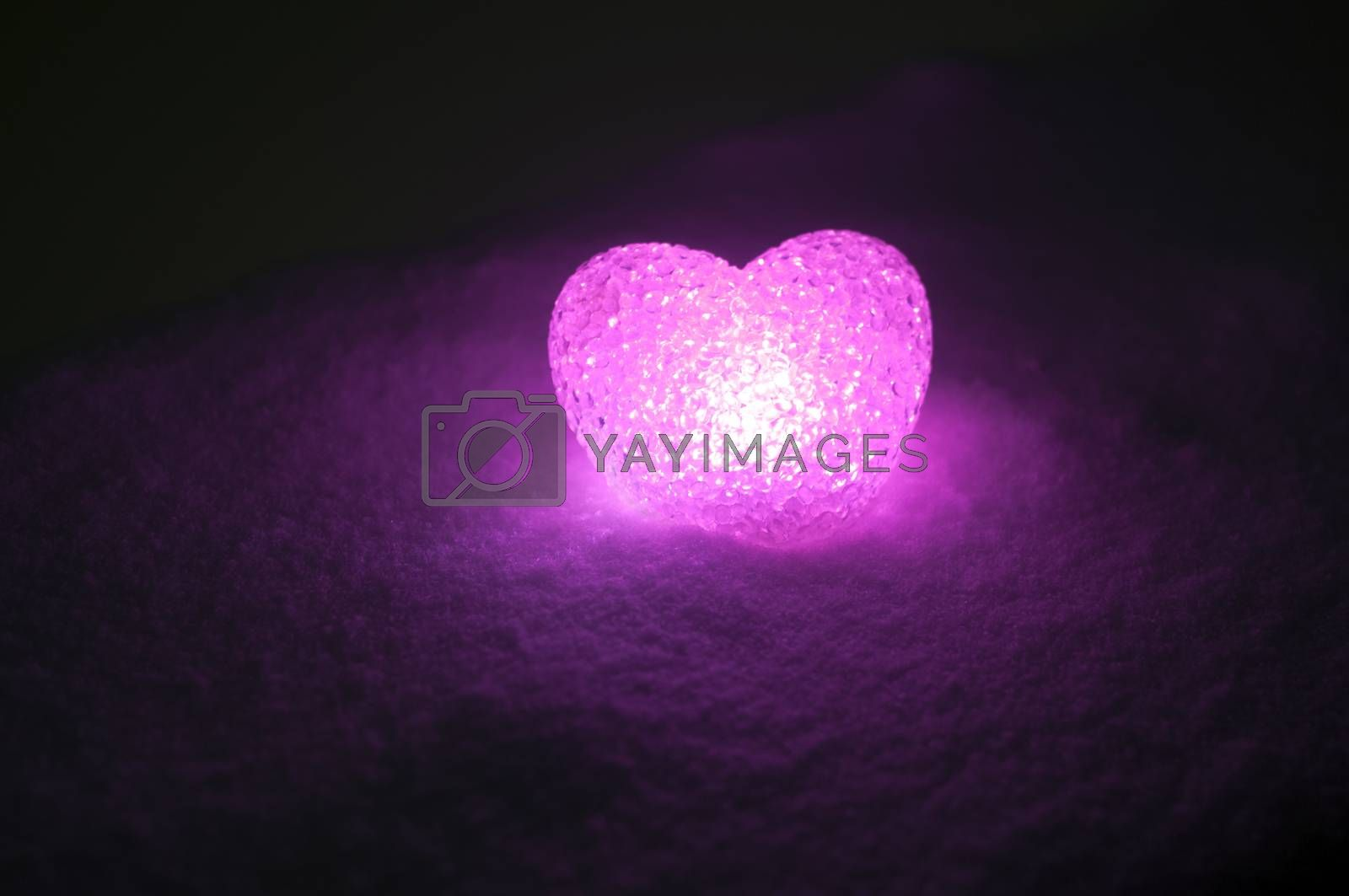 abstract glass heart on snow at night. Card for a Valentine's day. pink heart llight on black background