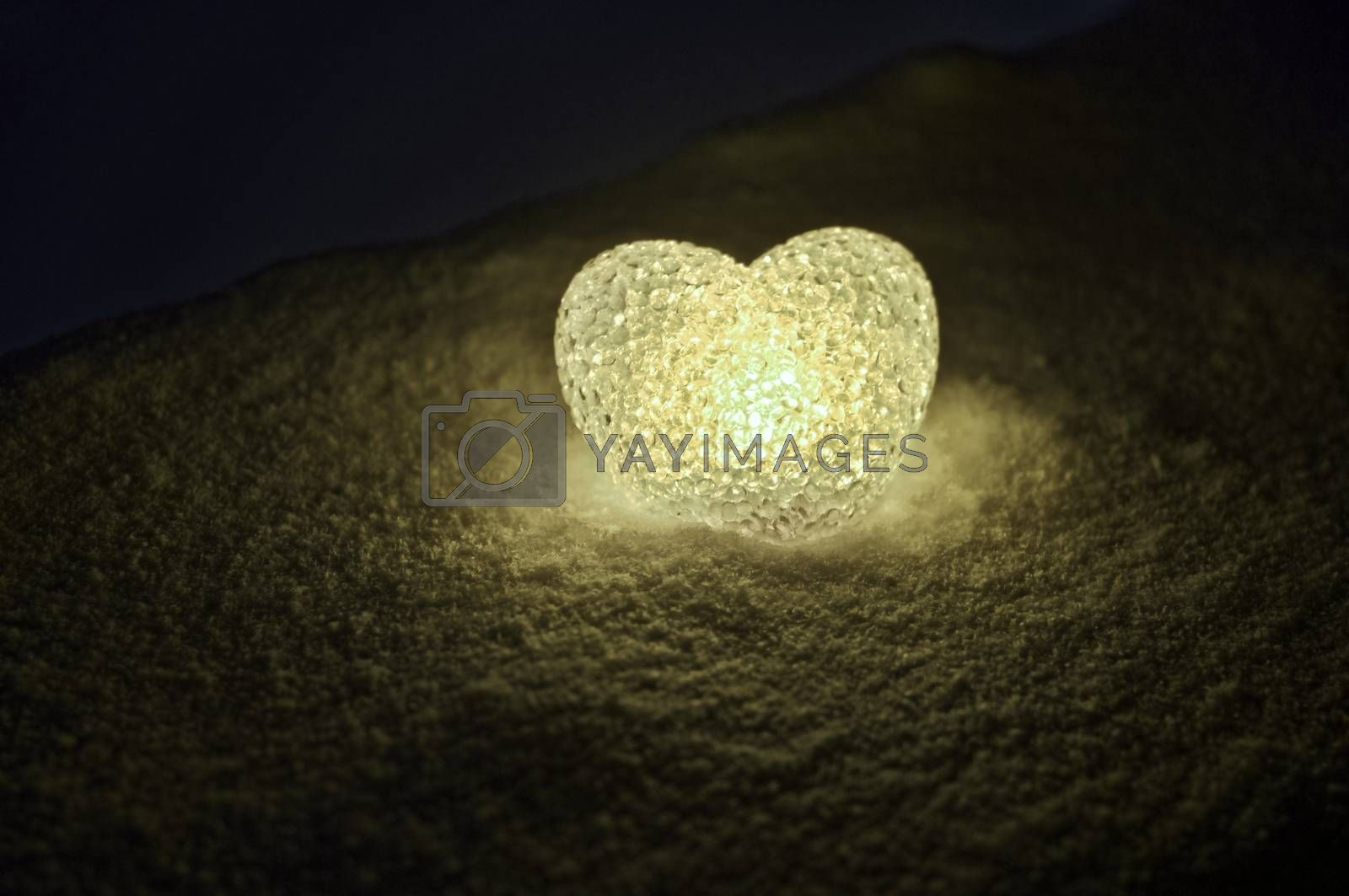 abstract glass heart on snow at night. Card for a Valentine's day. yellow heart llight on black background