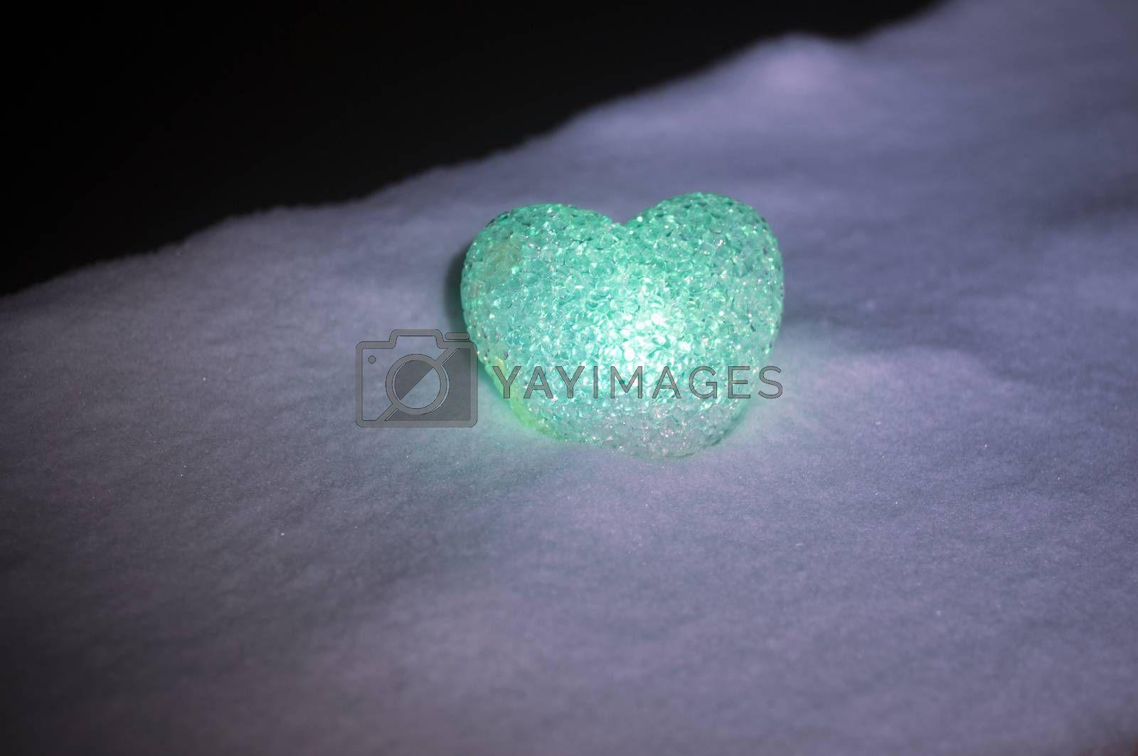 abstract glass heart on snow at night. Card for a Valentine's day. green heart llight on black background