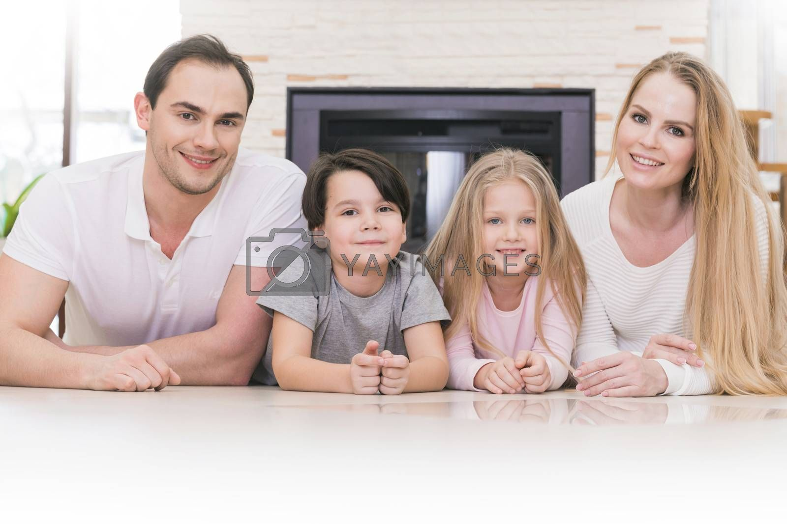 Portrait of four people family with children at home over chimney background