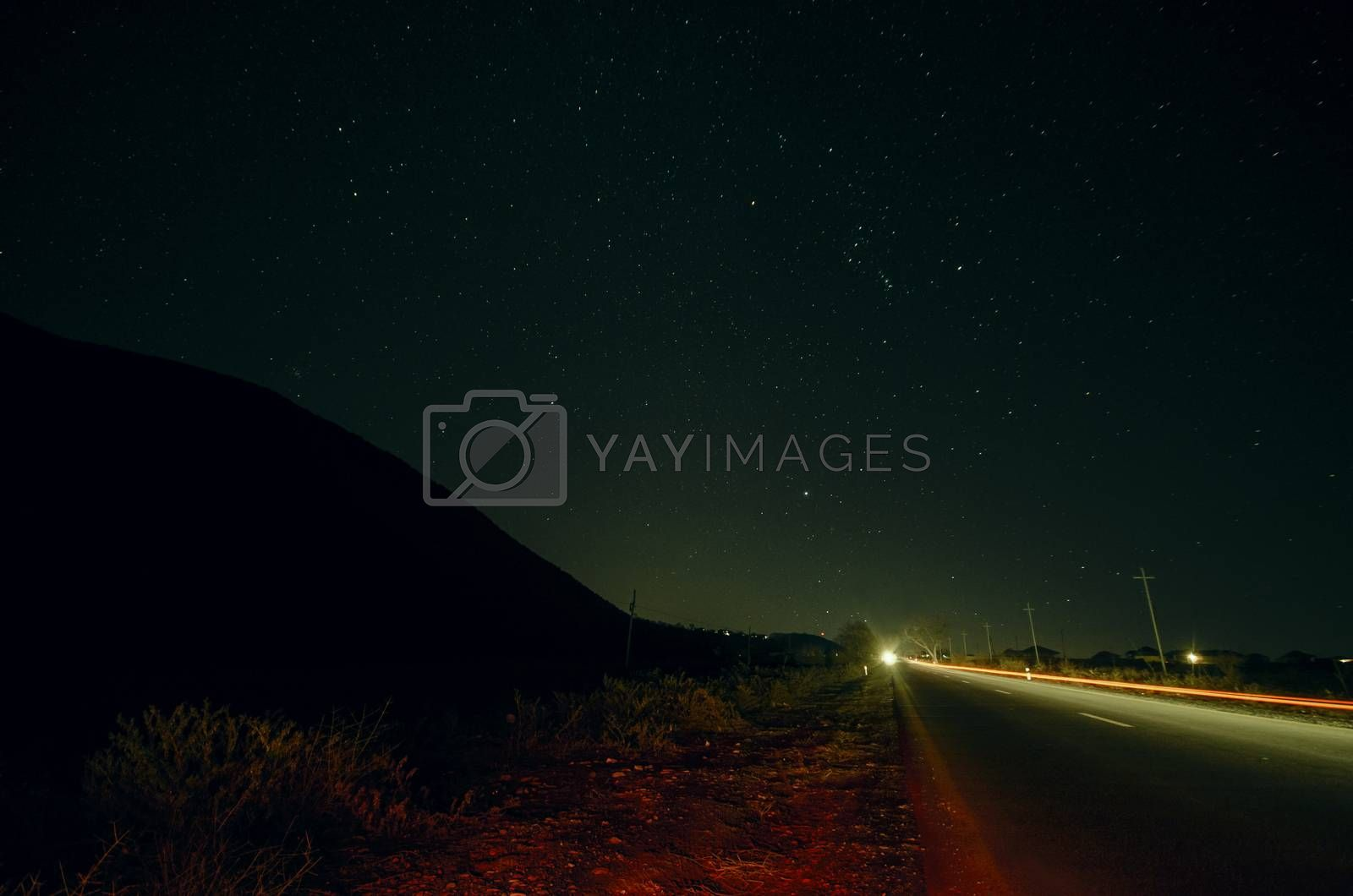 Beautiful night landscape of stars at sky and mountain silhouette near road with car trails. Road in the mountains under a starry gyres. Azerbaijan, Big Caucasus, Sheki