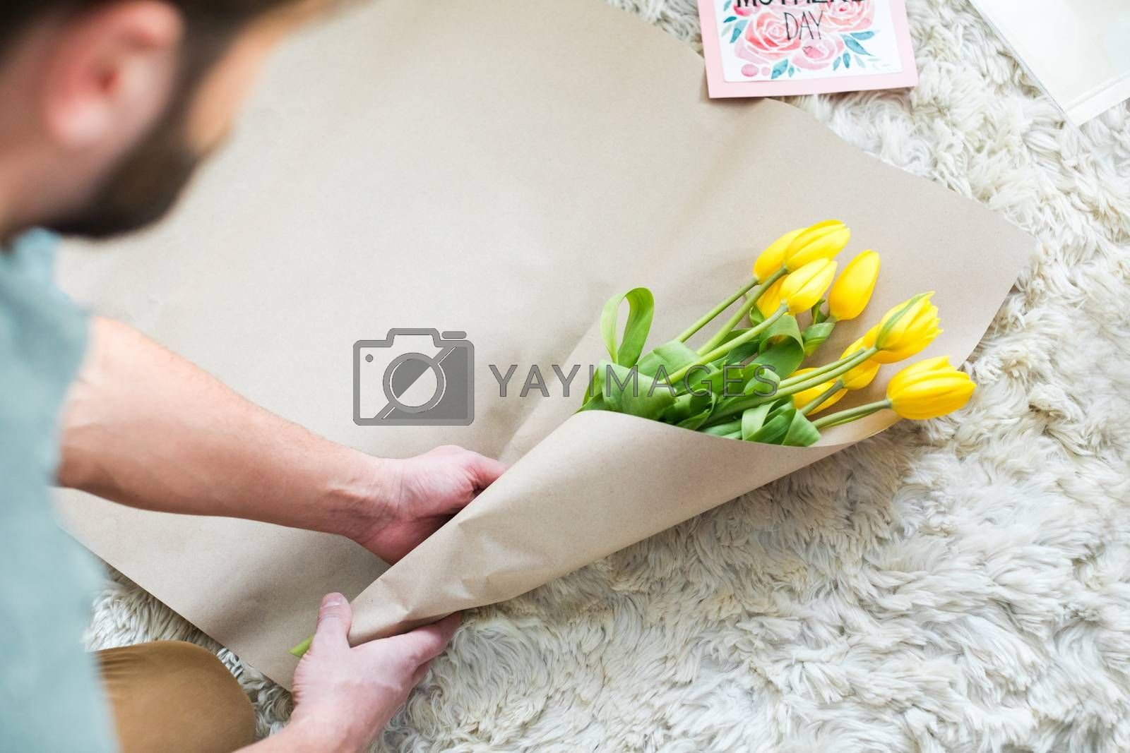 Partial view of man packing bouquet of fresh yellow tulips for Mothers Day