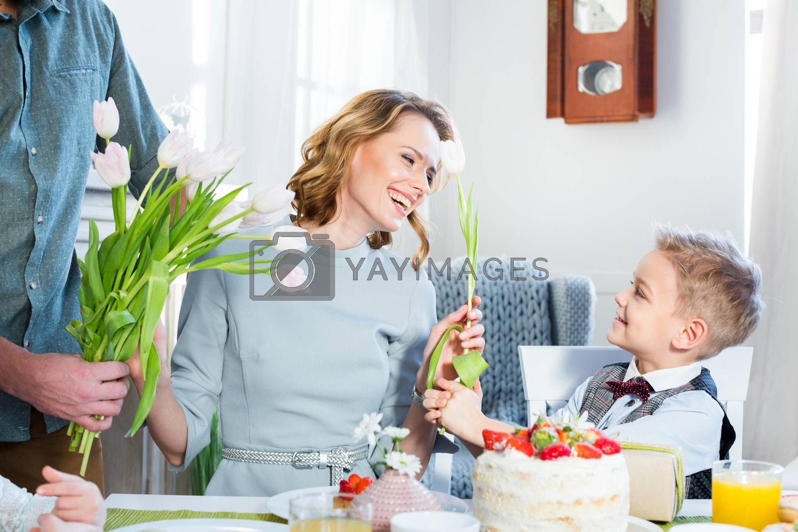 Young man and little boy gives fresh tulip flowers to happy woman