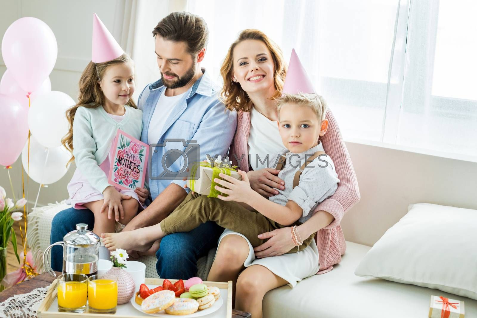 Happy family sitting together on sofa with present and greeting card for Mothers day