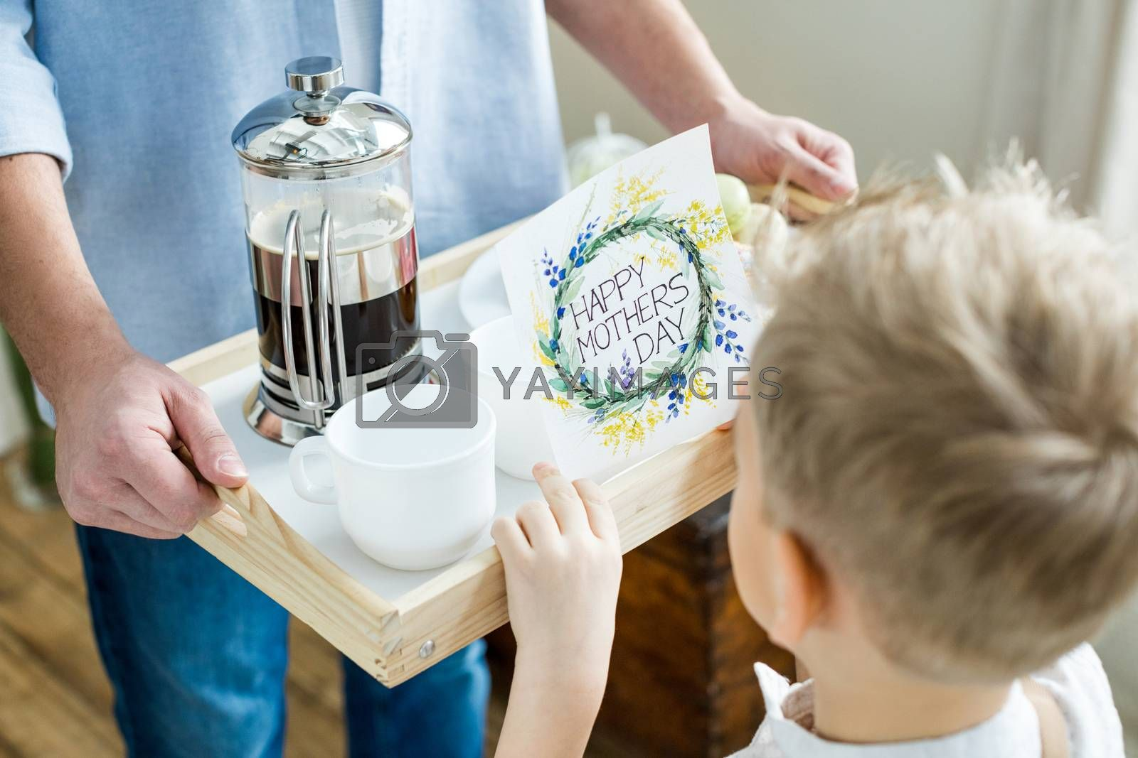 Partial view of father and son holding tray with coffee and happy mothers day greeting card