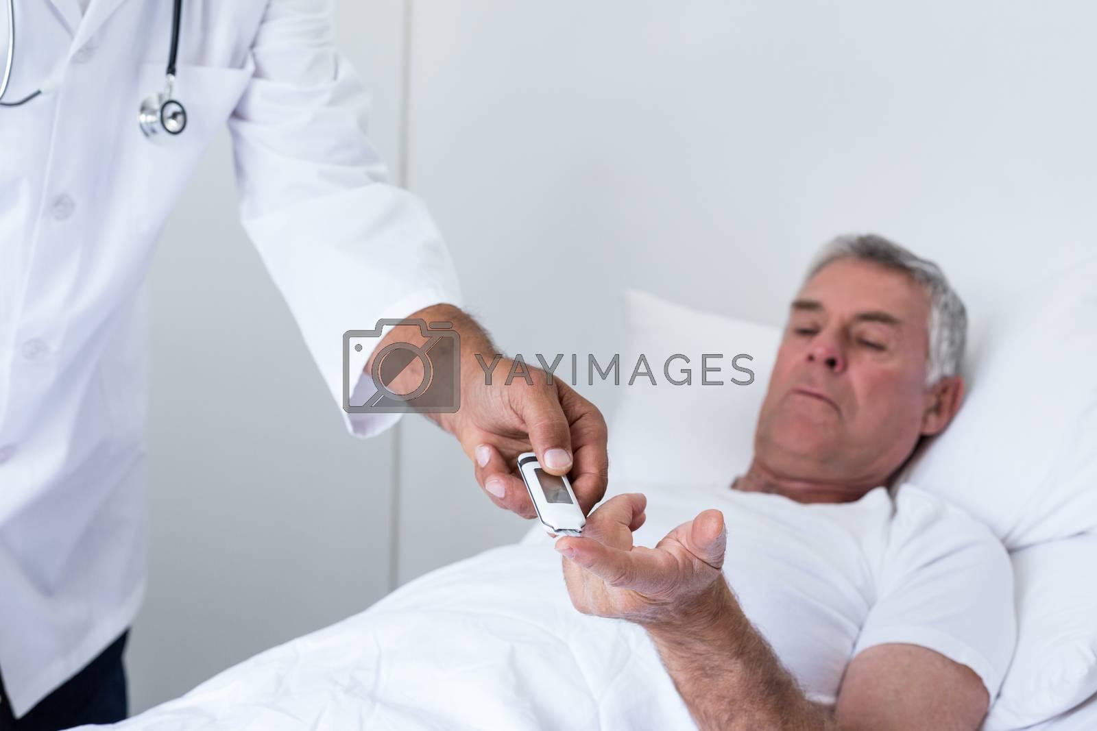 Royalty free image of Male doctor testing diabetes of senior man on glucose meter by Wavebreakmedia