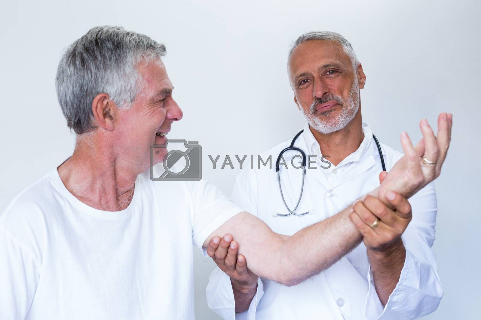 Royalty free image of Male doctor giving palm acupressure treatment to senior man by Wavebreakmedia
