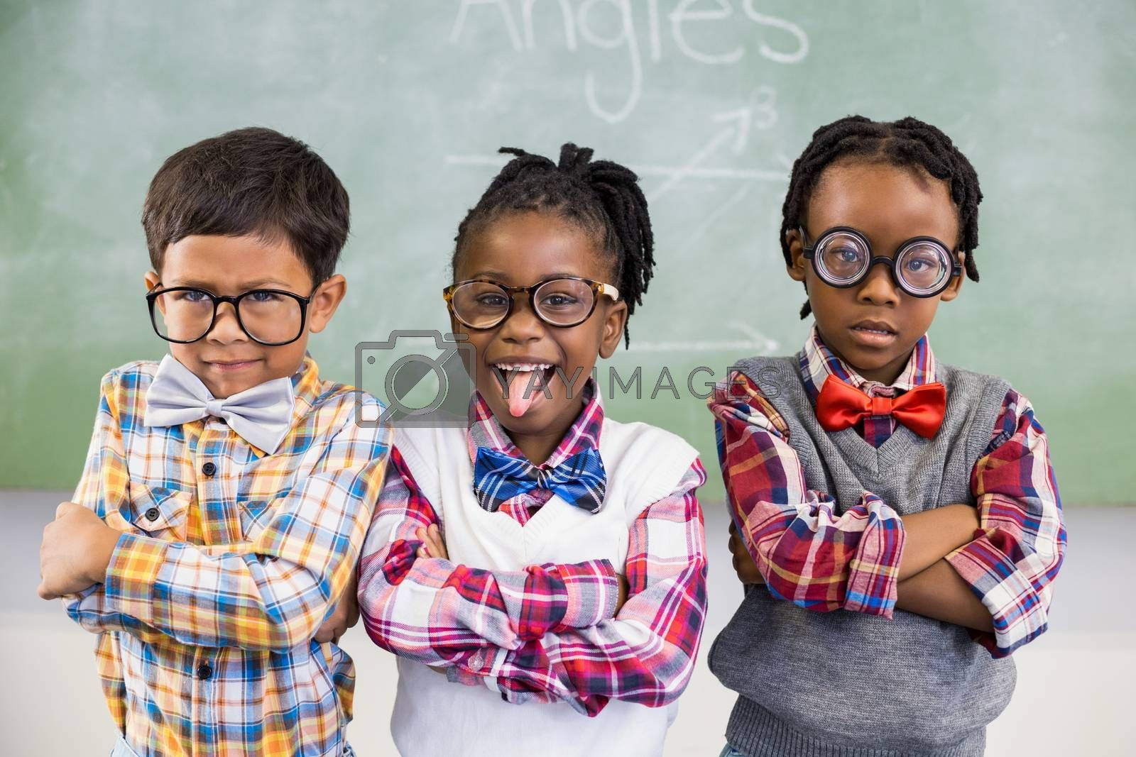 Portrait of three school kids standing against chalkboard in classroom