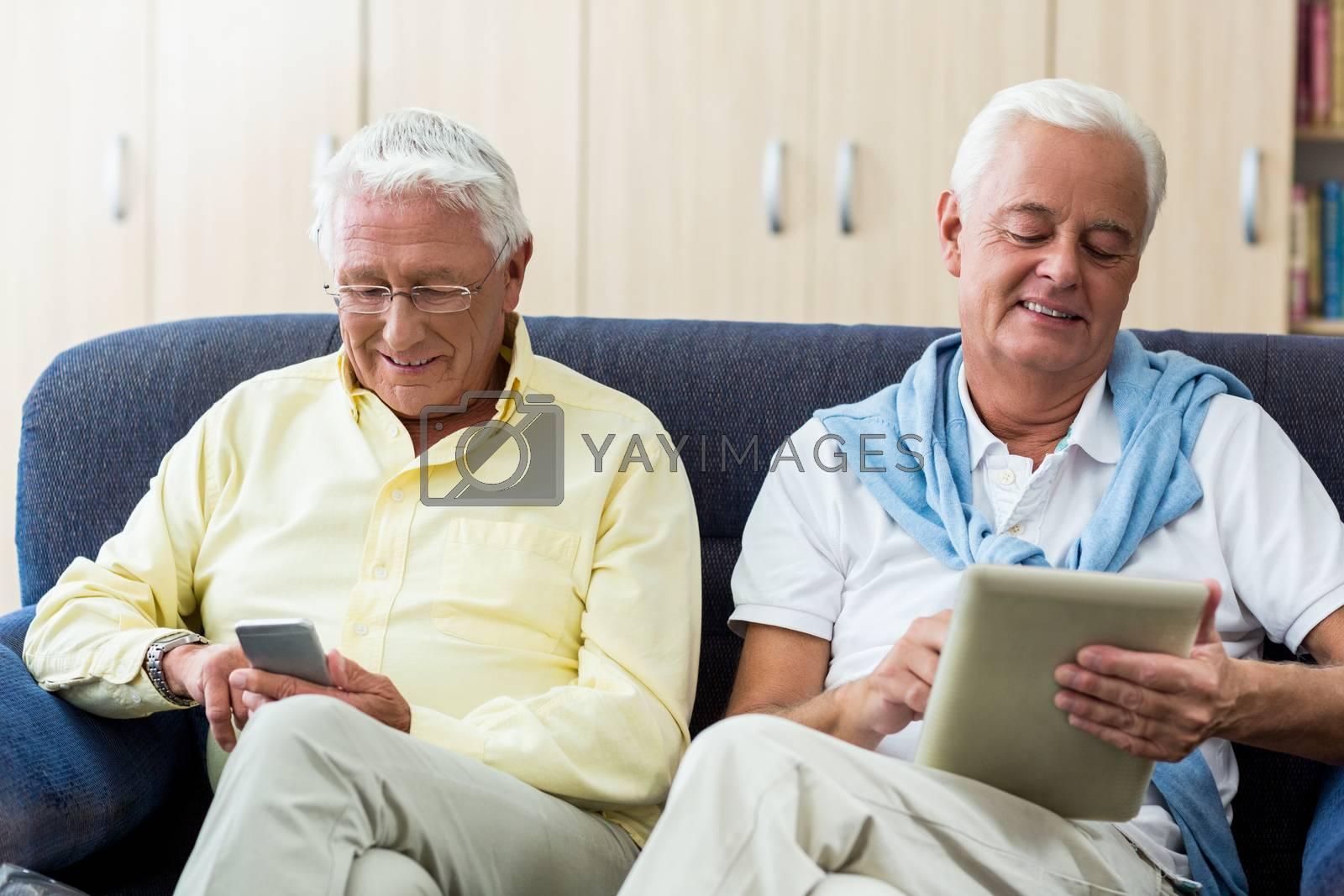 Senior men using technology in a retirement home