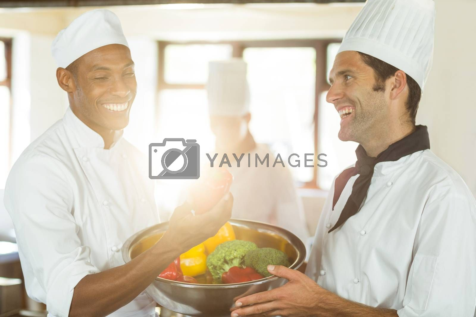 Two smiling chef holding a bowl of vegetable in commercial kitchen