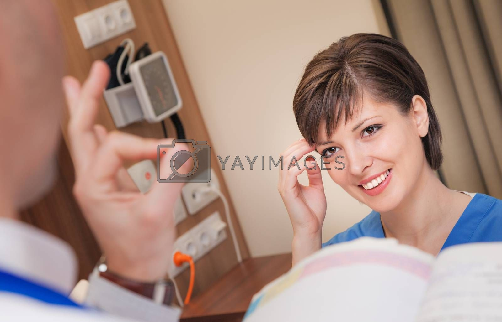 A doctor is showing an OK sign to a smiling beautiful young female patient in hospital room.