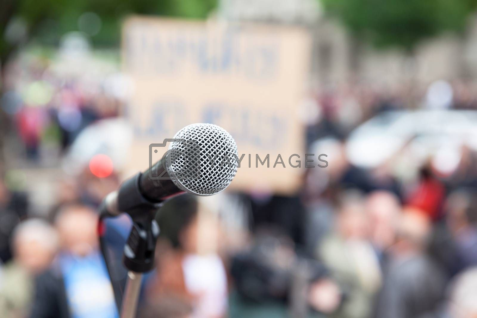 Microphone in focus, blurred crowd in background. Political rally.