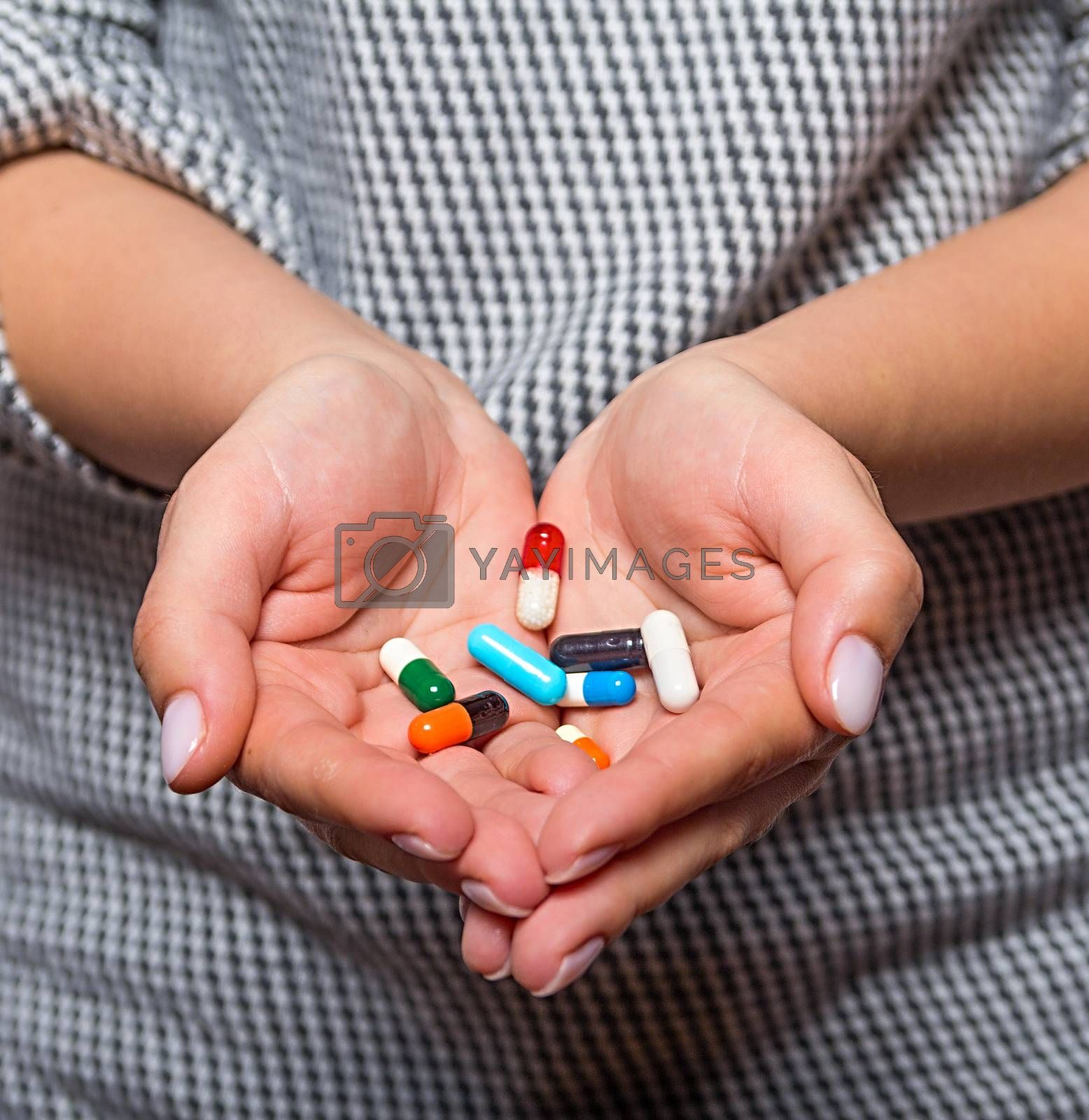 Woman arm holding heap of meds  before taking medication, focus on medicine