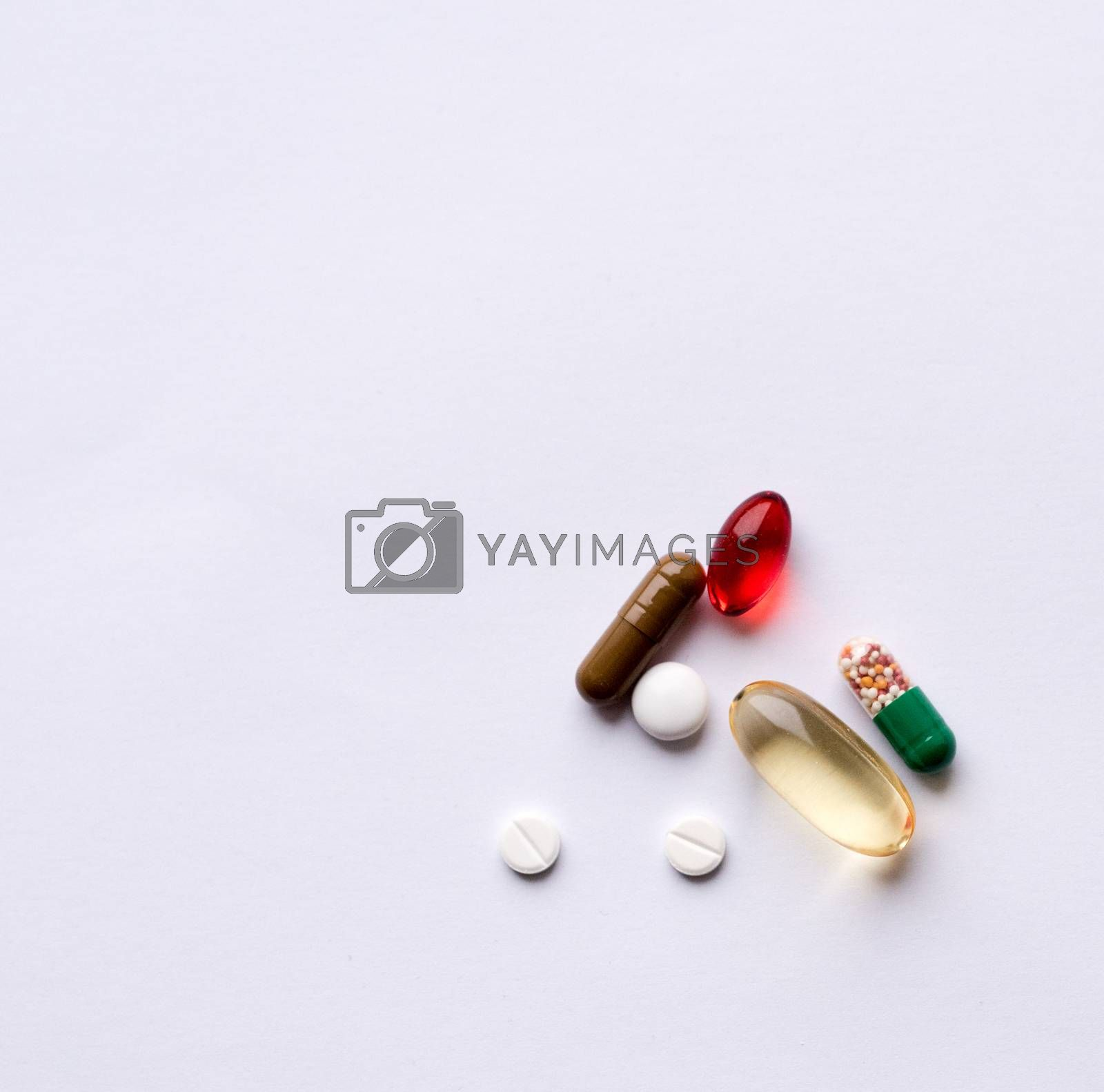 Tabs Vitamins, omega 3, Medications tablets and capsules in a beaker. Medications tablets, suppository bottles, capsules and thermometer on wooden table
