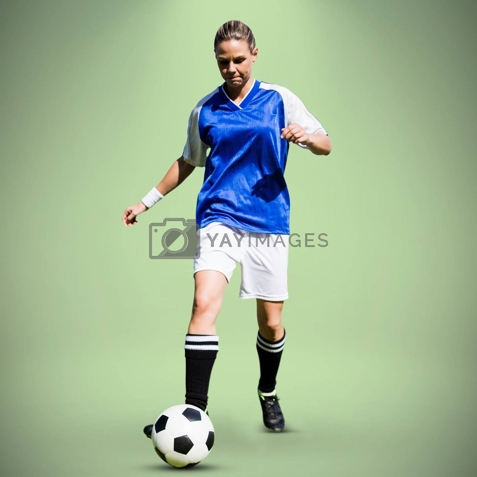 Woman soccer player progressing with a ball against green background