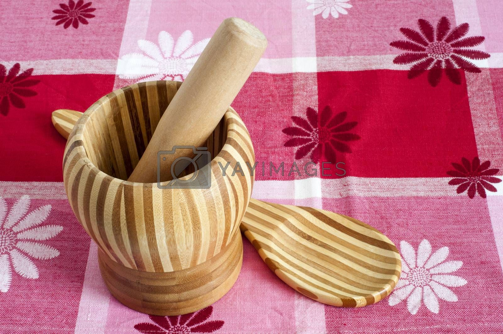 A mortar and a spoon with bamboo wood