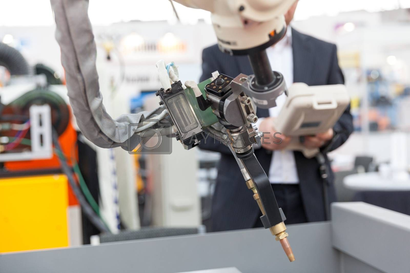 Industrial welding robot arm in the focus, blurred operator in the background