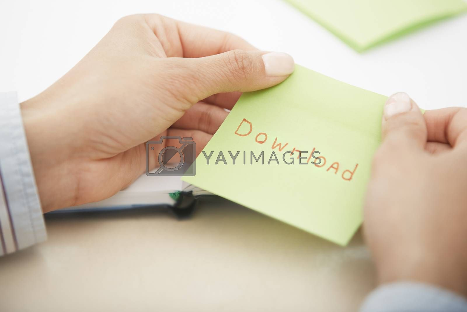 Hands holding sticky note with Download text