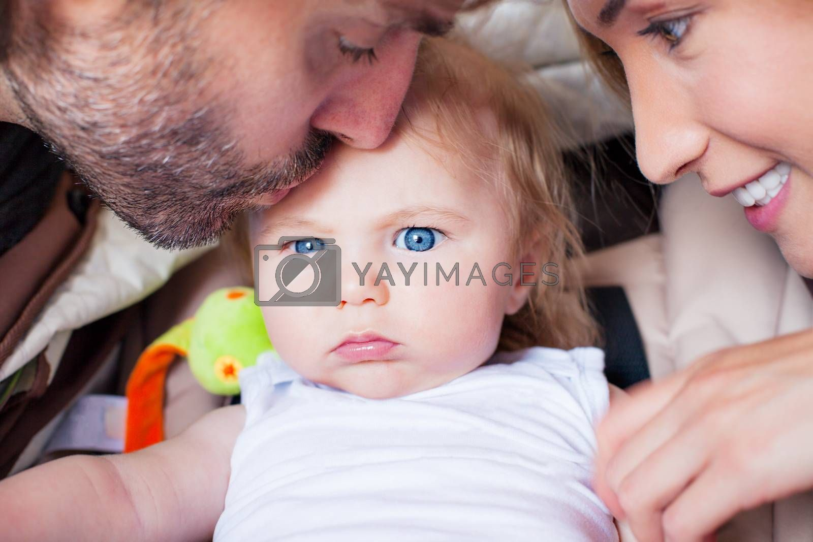 Frowning baby boy with big blue eyes is being kissed and pampered by his parents.