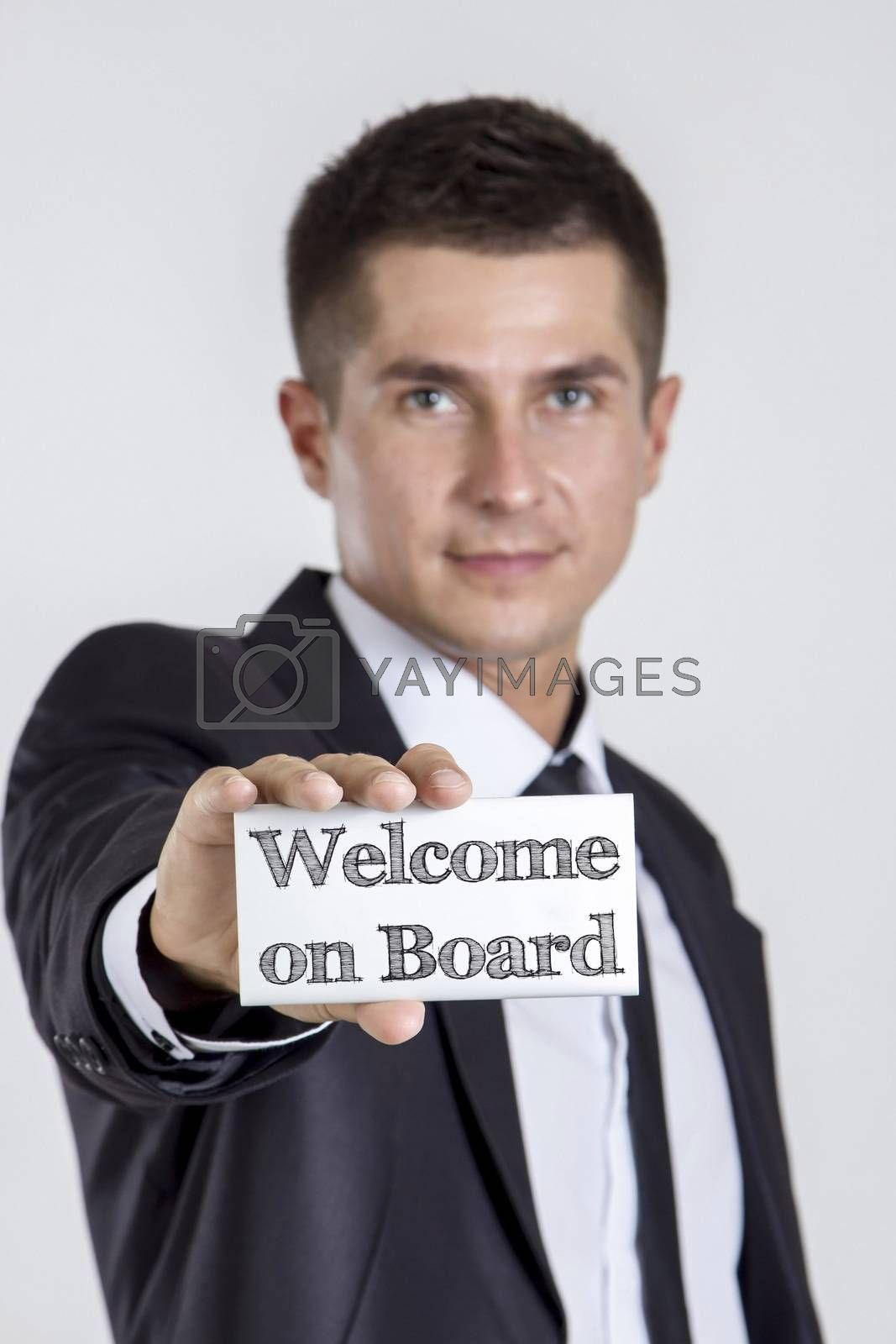 Welcome on Board - Young businessman holding a white card with text - vertical image