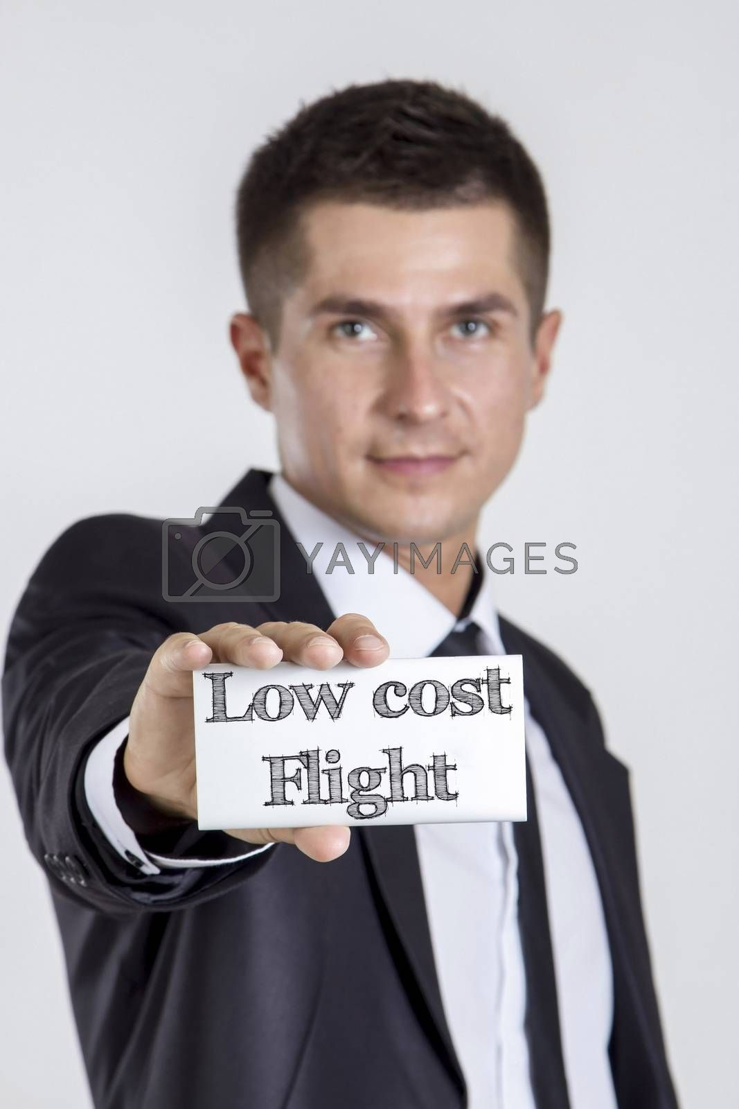 Low cost Flight - Young businessman holding a white card with text - vertical image