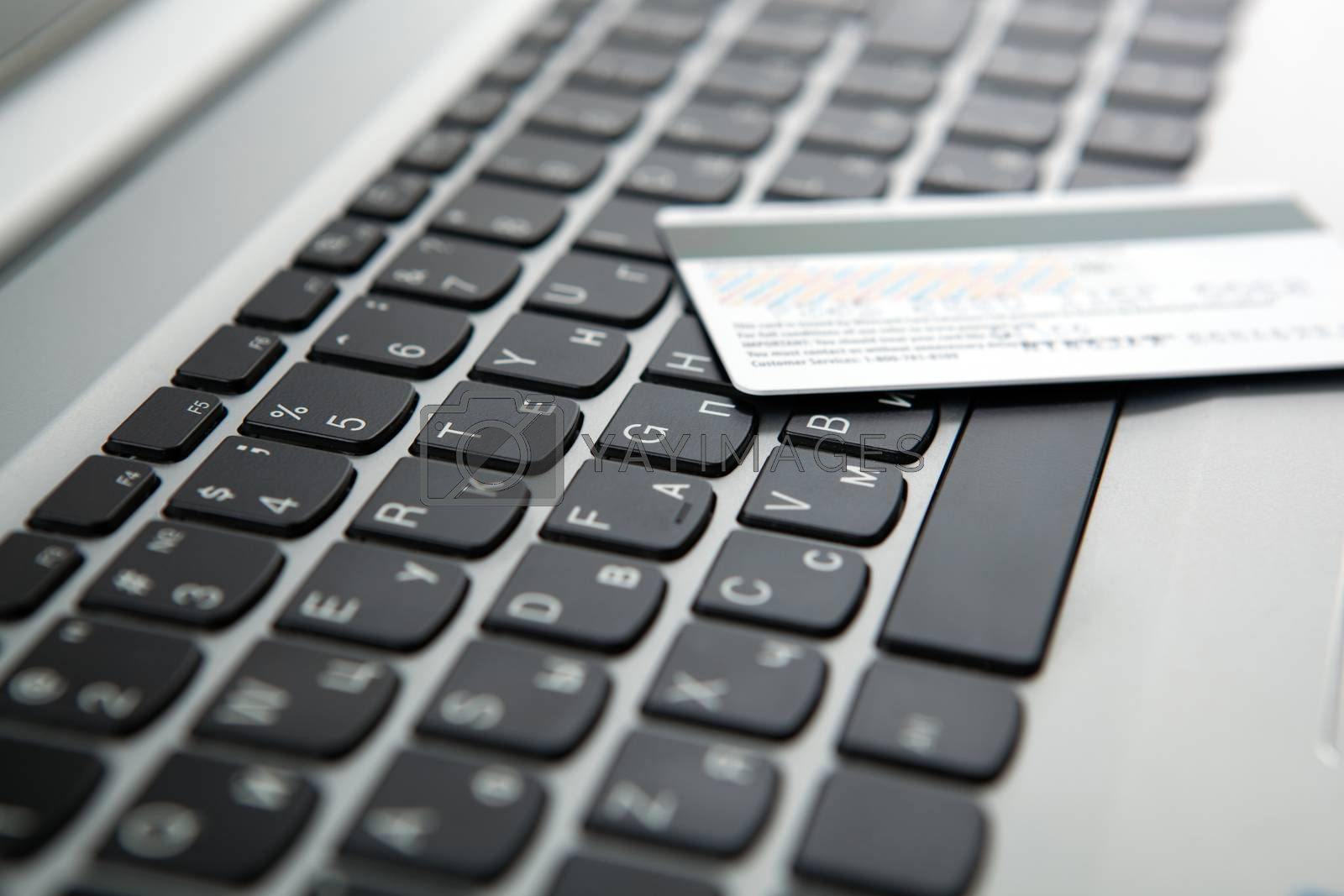 Royalty free image of bank card lies on the laptop keyboard by mizar_21984