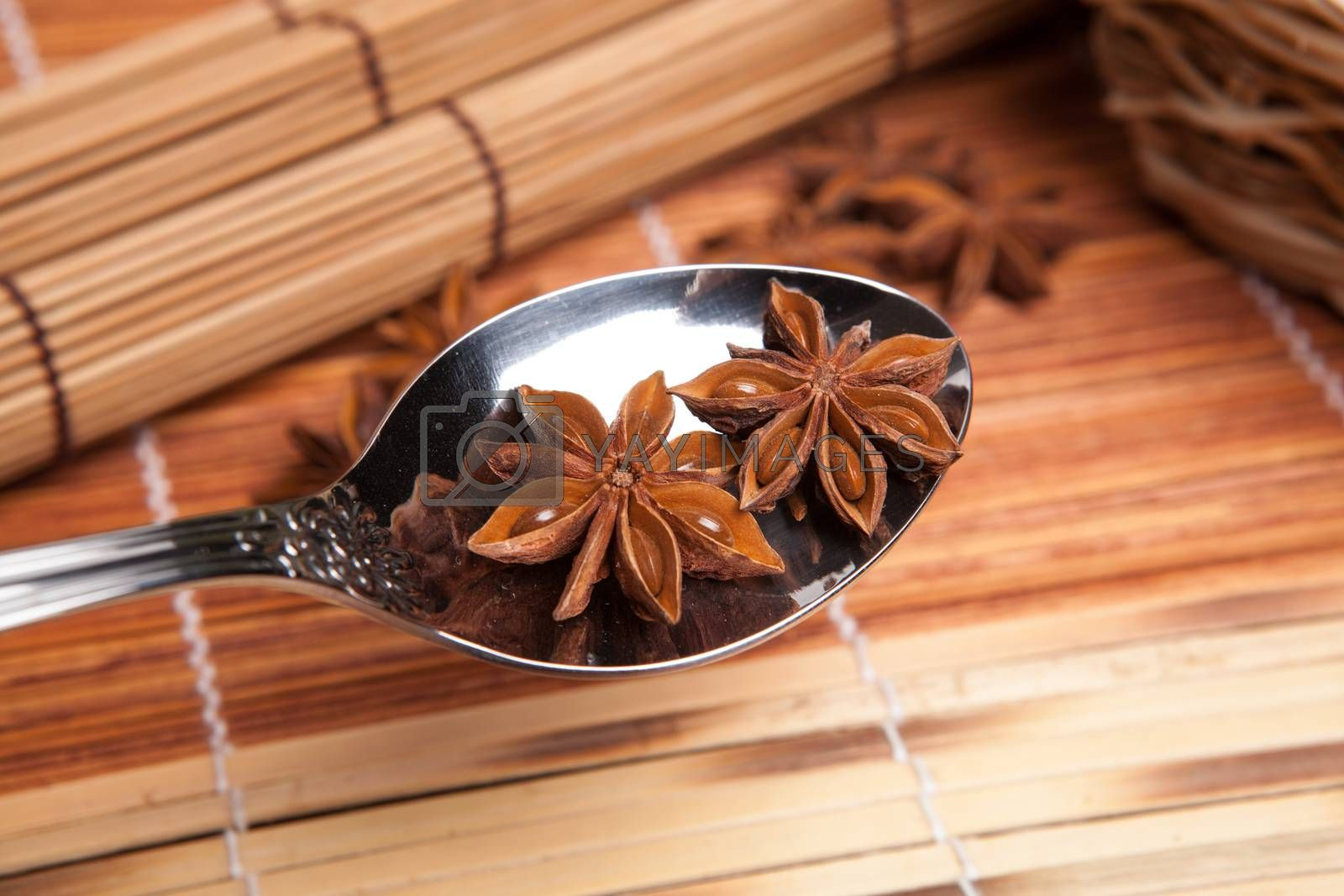 Royalty free image of two stars of anise in a spoon by mizar_21984