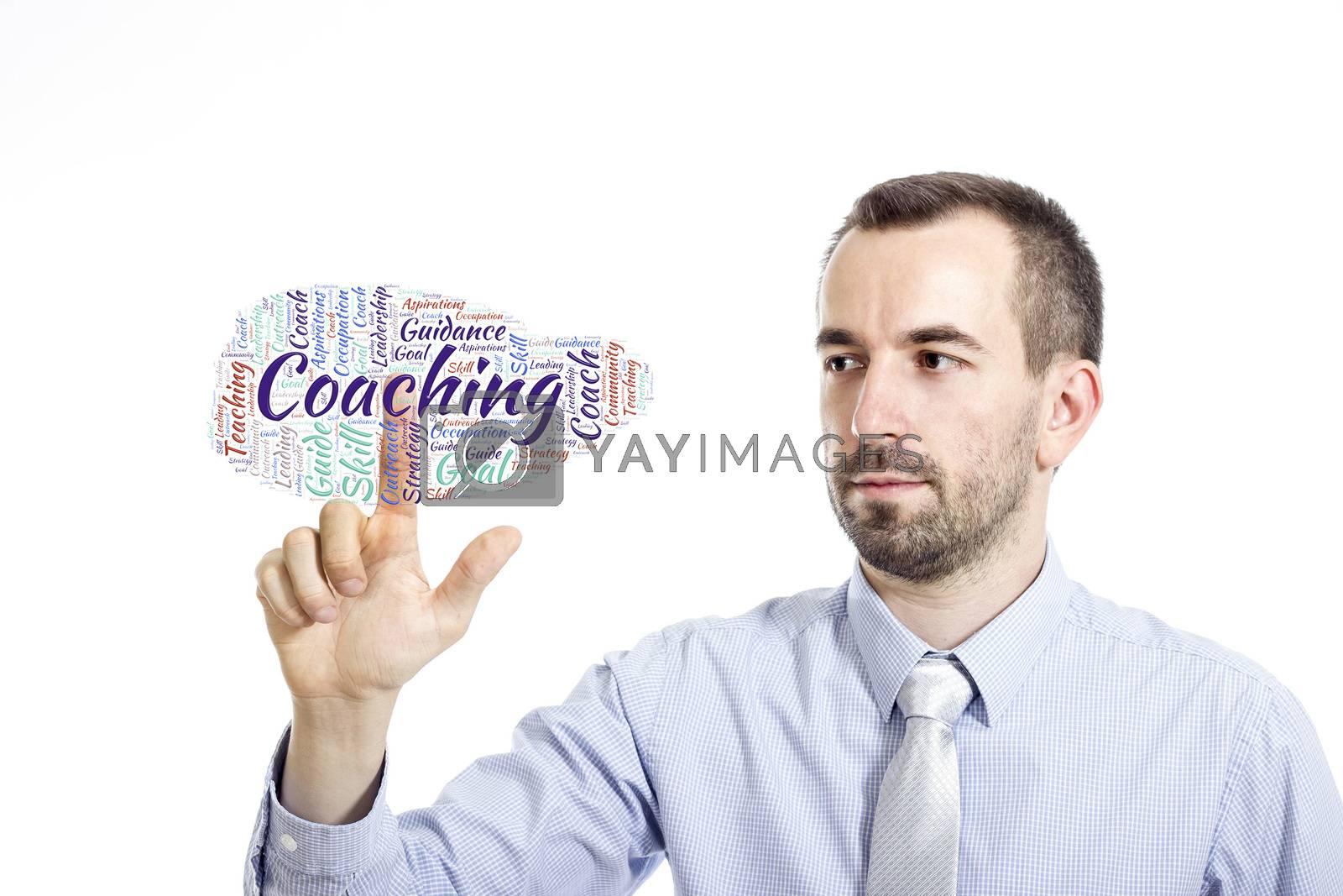 "Young businessman in blue shirt with small beard touching ""Coaching"" word cloud"