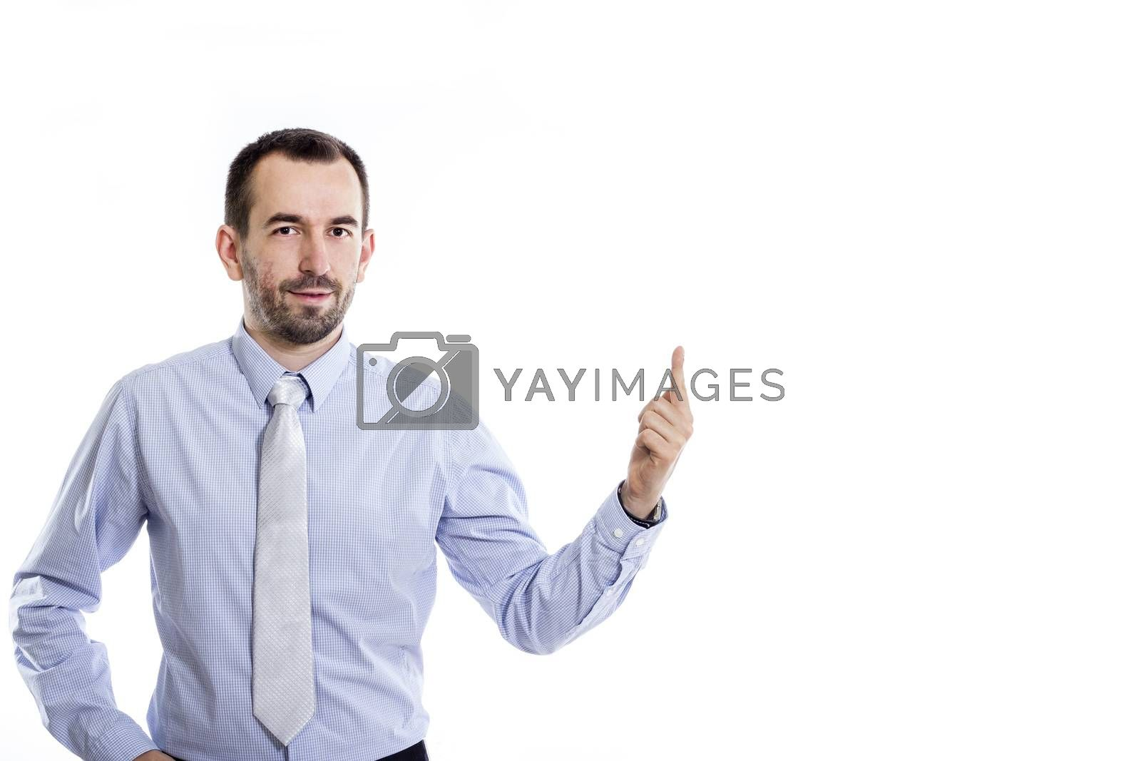 Young buinessman with small beard pointing up in blue shirt with copy-space