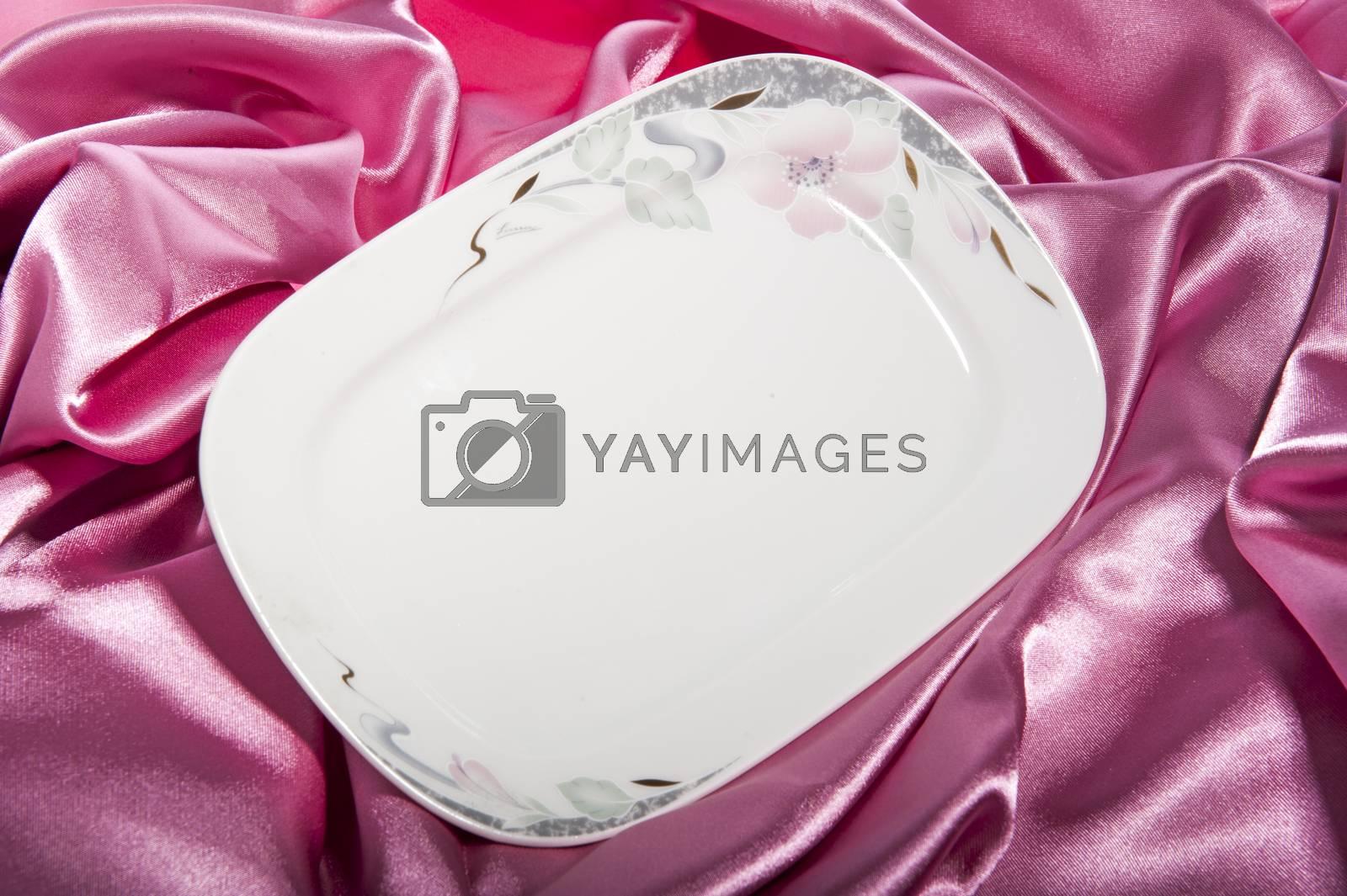 a elegant ceramic plate on a  fabric backgroun
