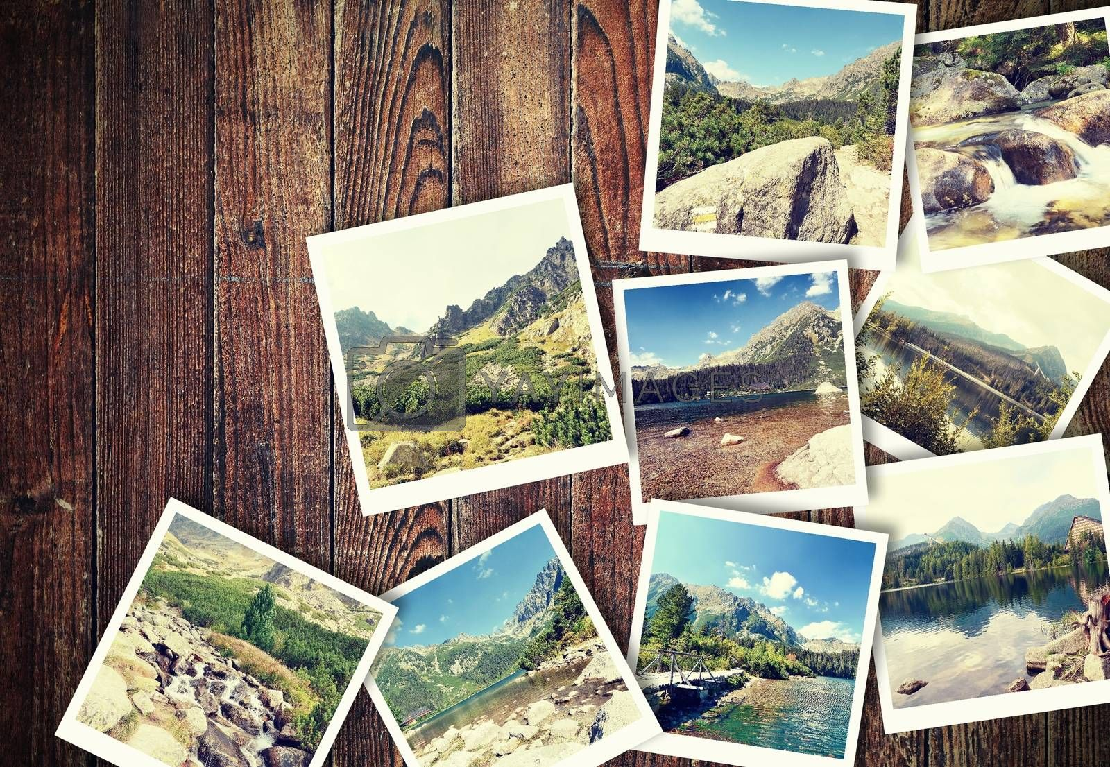 Heap of the vintage photos from holiday in mountains with traditional white frame placed on wooden desk.