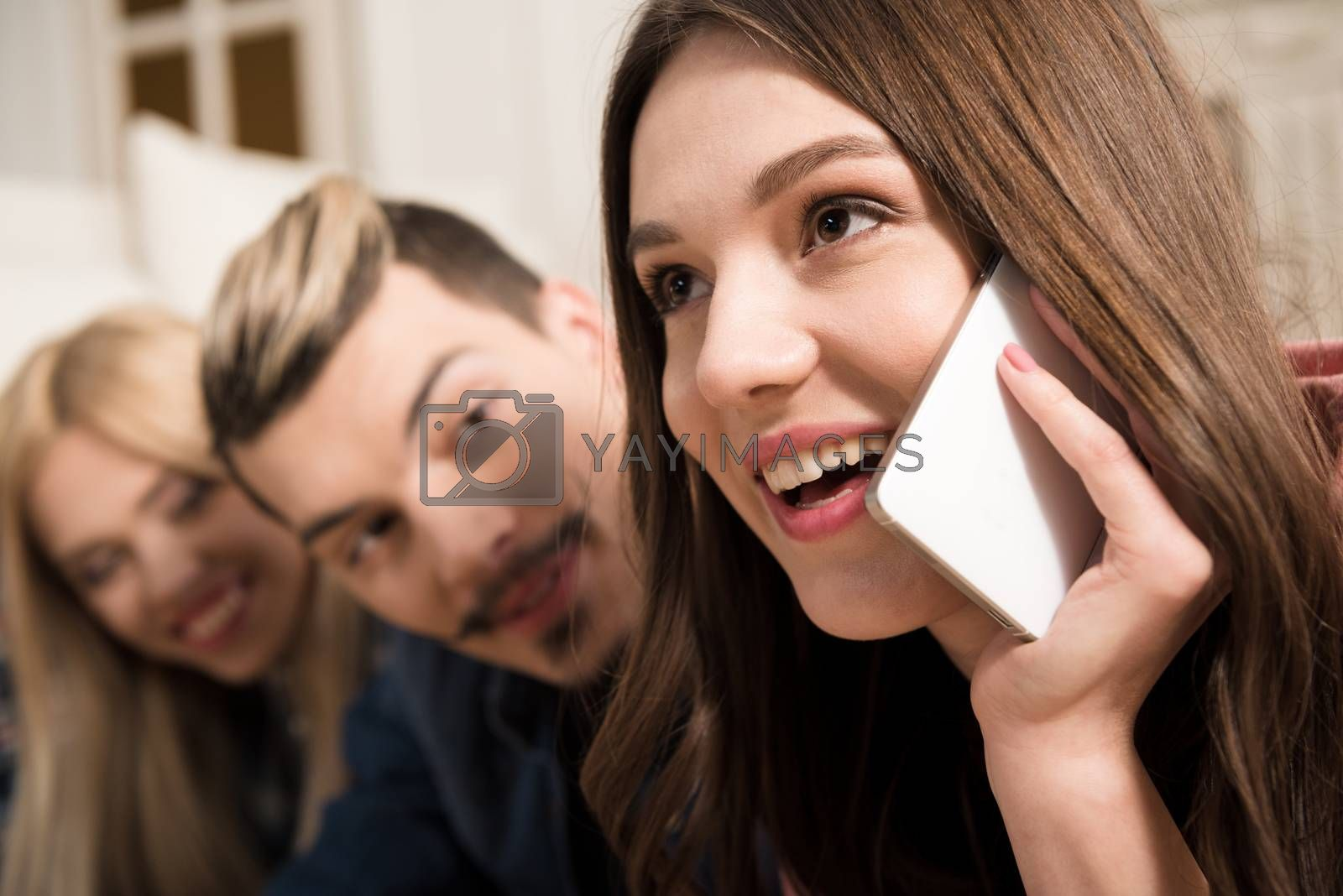 Smiling young friends looking at beautiful happy woman talking on smartphone