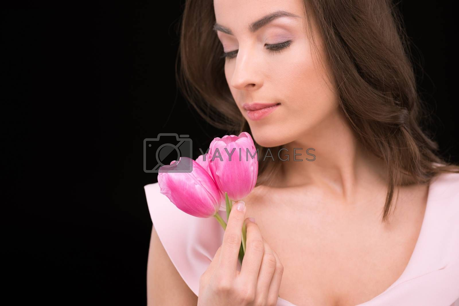 Gorgeous young woman holding beautiful pink tulips on black, international womens day concept