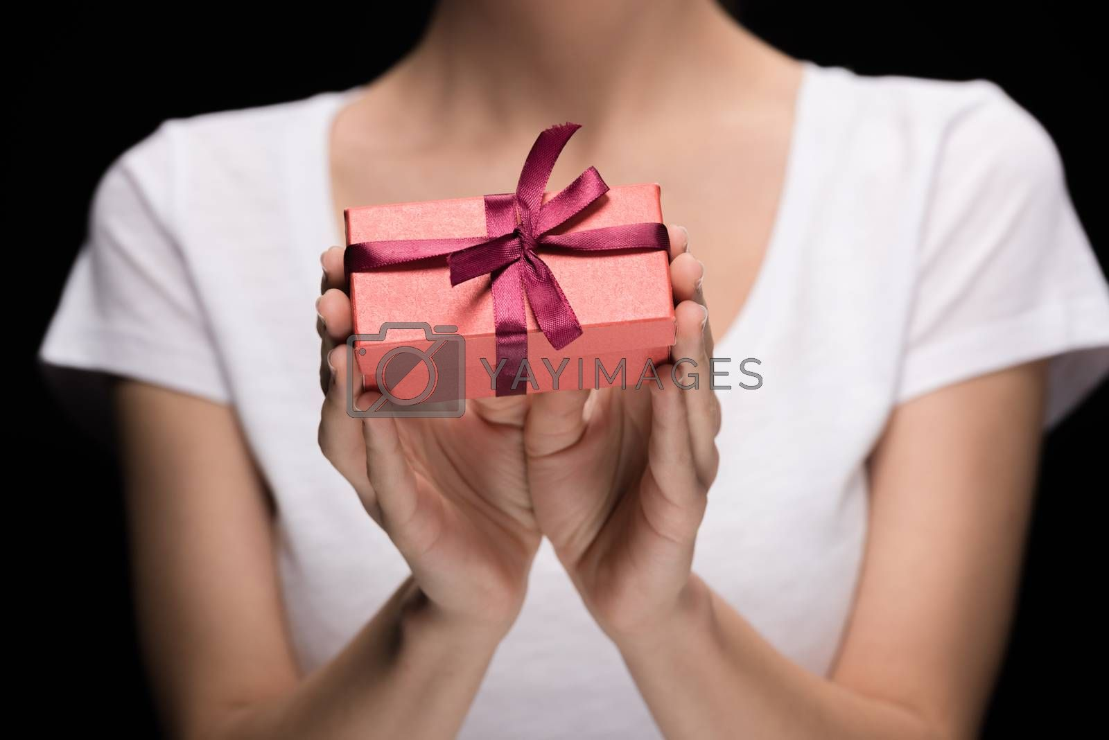 partial view woman showing gift in hands on black, international womens day concept